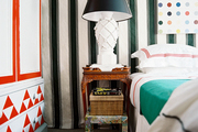 Striped walls and a red-and-white armoire in a bedroom