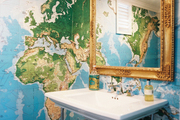 Map wallpaper and a gold mirror in a bathroom