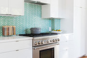 Contemporary white kitchen with teal tile.