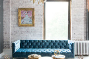 Tufted couch and matching gold furnishing in front of painted brick wall.