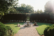 A fountain on a gravel path in a yard surrounded by Leyland cypresses