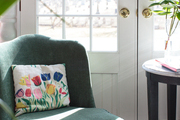 A floral pillow rests on a green chair near a sunny door
