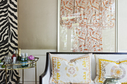 A framed kimono hung above an upholstered settee