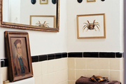 Artwork and a gold-framed mirror in a bathroom with square vintage tile