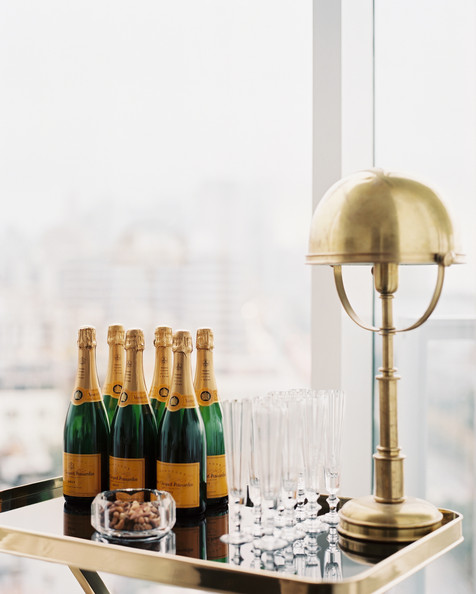 Bar - Champagne, glassware, and a brass lamp on a tray table