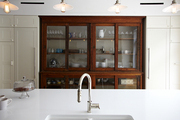 A vintage glass-front cabinet displays and provides storage for dishes in a modern kitchen.