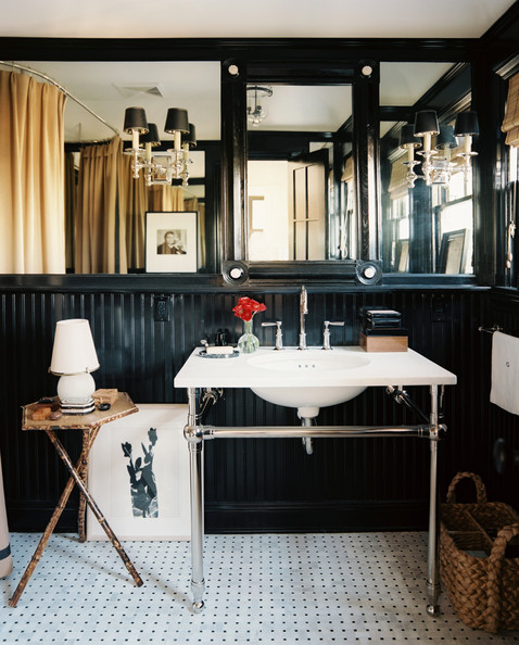Beadboard - A black bathroom with mirrored panels and a pair of double-arm sconces