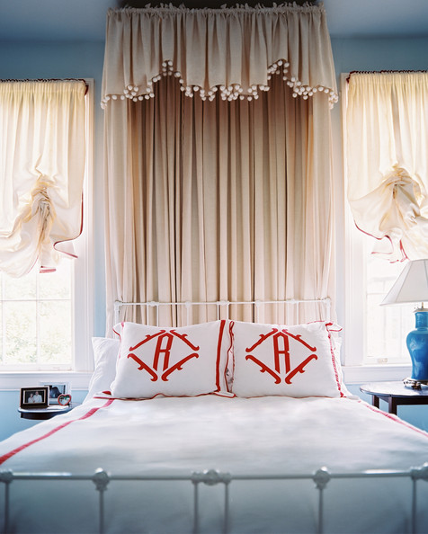 Bedroom Blue - A pompom-fringed canopy above monogrammed bed linens