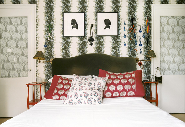 Bedroom - Silhouettes hung on floral wallpaper above a green velvet headboard