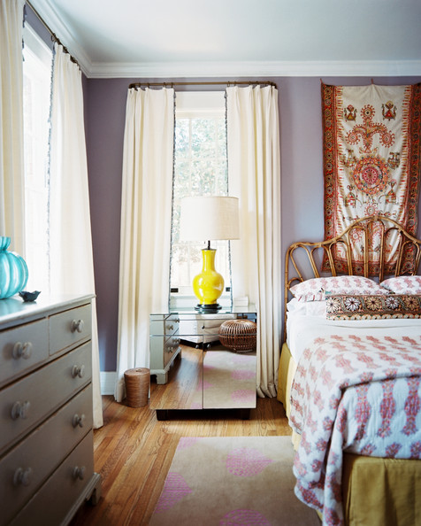 Bedroom - A rattan headboard with patterned bedding beside a mirrored bedside table