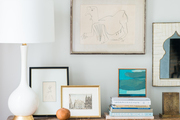 A detail of a Bohemian console table with framed artwork, books, and a modern white and gold lamp.