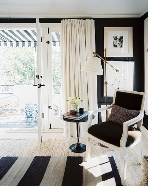 Black living room layered rugs and a brass floor lamp in for Mark d sikes living room