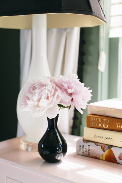 Books - Ruffled blooms on a nightstand next to a table lamp