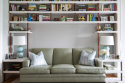Tall white shelving above green couch.