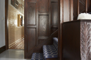 A wood paneled stairway with a printed runner carpet.