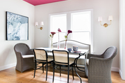 A contemporary dining space with a pink ceiling and gray armchairs.