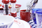 Salt=and=pepper shakers, a red mug with silverware, and blue glasses