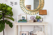 A weathered gold mirror above a foyer table