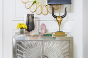 A console topped with a table lamp, vases, and decorative objets; wall art above