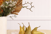 A close-up shot of pears sitting on a plate, on top of a wooden table.
