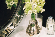 A vase of flowers beside an oval mirror