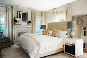 A tufted headboard and white bed linens in a neutral master bedroom