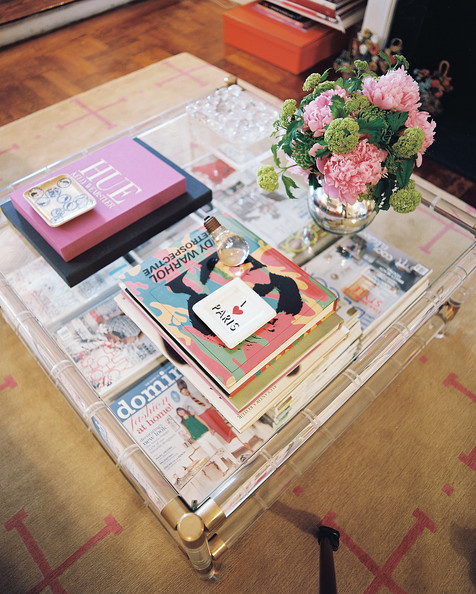 Coffee Table - A Lucite coffee table covered with books and a vase of flowers