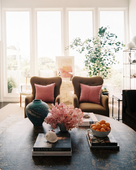 Coffee Table - A pair of tan armchairs with pink pillows