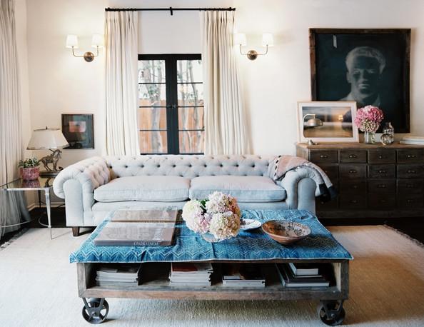 Coffee Table - A tufted couch arranged with a factory-cart coffee table