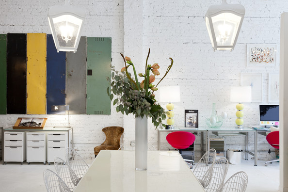 Conference Table - A white conference table and wire-backed chairs under white pendant lights