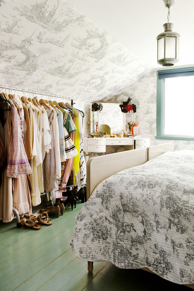 Country Closet - Toile wallpaper and a rolling rack of clothes in a bedroom