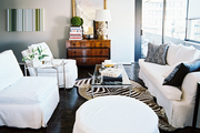 A living space with white furniture and a glass-topped coffee table on a zebra-hide rug
