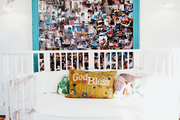 A white daybed and a multicolored rug paired with a framed collage of photos