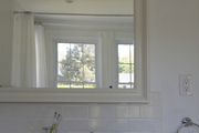 Framed Mirror and white tiled splashboard above marble countertop sink.