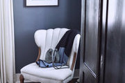 A detail of a white chair in a bedroom against a blue wall.