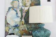 A vignette featuring a table lamp, an oil painting, and various decorative objets