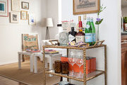A stocked bar cart in an apartment foyer