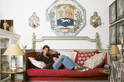 Carolina Irving on a red daybed in her Manhattan apartment