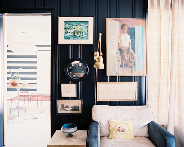 Dark Walls - Art and a brass-arm sconce on black walls
