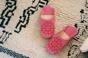 Pink slippers atop a patterned carpet
