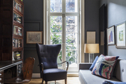A wingback chair and a wooden bookcase in a study