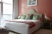 Large headboard and colorful throw pillows atop white bedding.