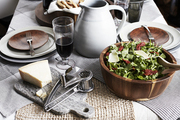 A cheeseboard, salad, and wine compliment a rustic pizza party