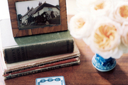 Books and a vase of flowers atop a wooden surface