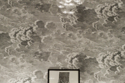 A bubble chandelier above artwork and cloud-patterned wallpaper
