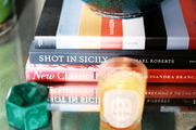 A stack of books and a malachite decorative object atop a mirrored surface
