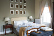 A grid of framed prints above a bed with upholstered headboard