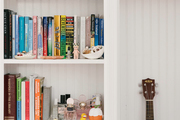 A bedroom bookshelf space with a mini guitar on display.