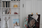 A portrait painting next to white built-in shelving.