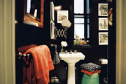 A bathroom with black walls, a white pedestal sink, and a green garden stool